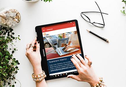 Tablet z przykładem newslettera PR-owego trzymany w ręku przez kobietę na tle biurka